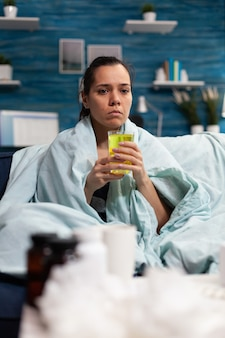 Кавказская женщина сидит дома, принимая лекарство от вирусной инфекции, когда чувствует себя больным взрослым ...