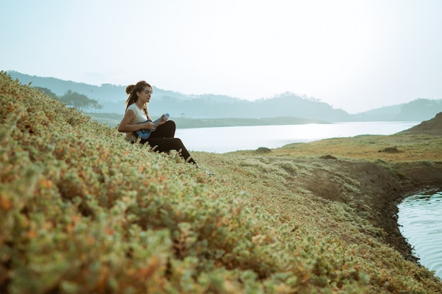 Caucasian woman sitting by a lake with blanket