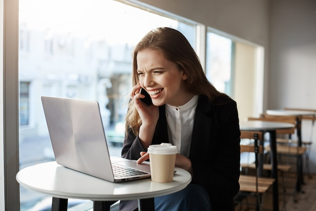 Caucasian woman sitting in cafe, drinking coffee, talking on smartphone, looking at laptop screen with broad smile