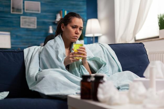 Donna caucasica seduta a casa che prende medicine per l'infezione da virus mentre si sente male. adulto con febbre raffreddore e influenza, sintomi stagionali a letto con tosse e mal di gola.
