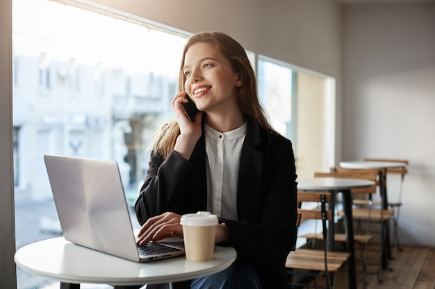 백인 여자 노트북과 카페에 앉아 커피를 마시는 스마트 폰 이야기