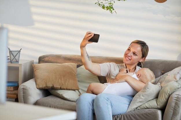ソファに座って、赤ちゃんの息子を腕に抱きしめながらスマートフォンで自分撮り写真を撮る白人女性