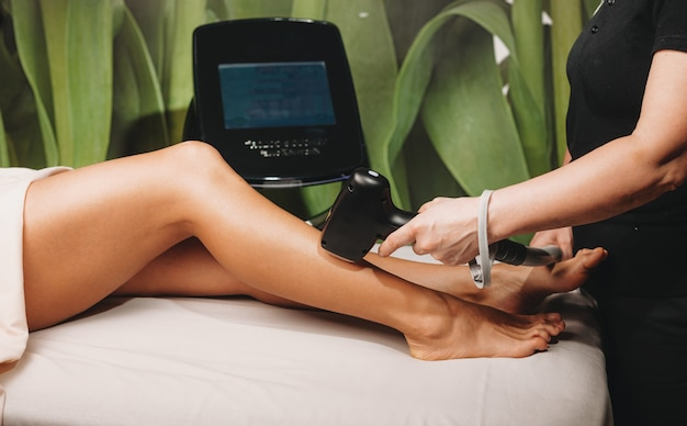 Кавказская женщина сидит на спа-кушетке и делает процедуру эпиляции ног в оздоровительном центре с современным оборудованием