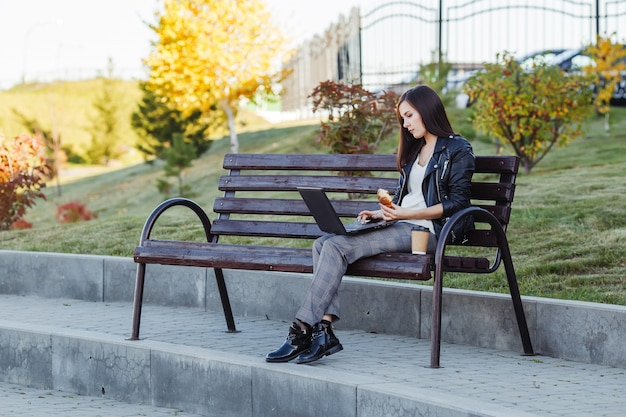 Caucasian woman sitting in park with laptop and eating croissant