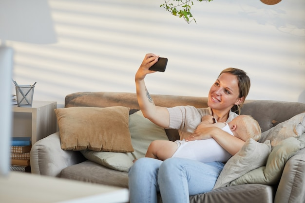 Caucasian woman sitting on sofa taking selfie photo on smartphone while cuddling her baby son in arms