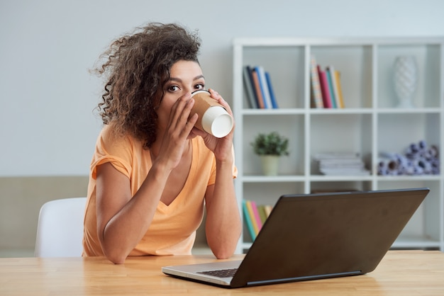 Caucasian woman sitting at table at home with laptop and drinking takeaway coffee