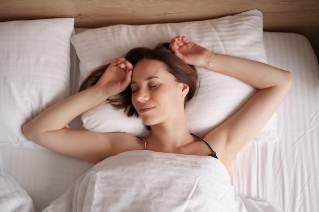 Кавказская женщина спит в постели. леди наслаждается свежим мягким постельным бельем и матрасом в спальне.