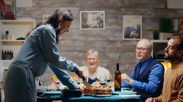 Donna caucasica che affetta la torta per il suo compleanno alla cena di famiglia.