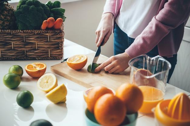 칼을 사용하여 집에서 신선한 주스를 만들기위한 과일을 자르는 백인 여자