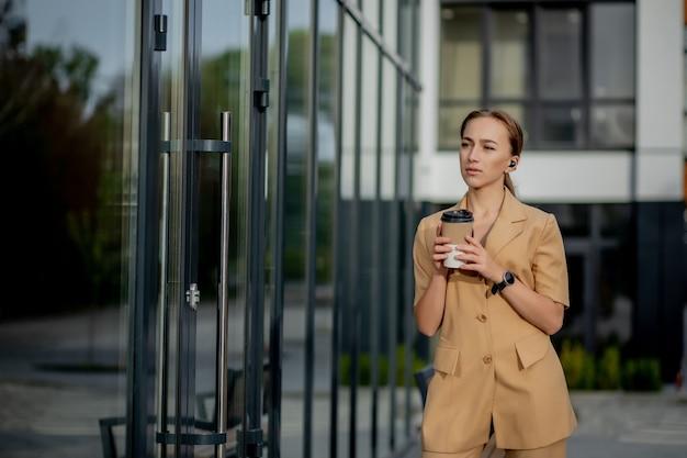 通りの建物に立っている白人女性のスマートフォン。