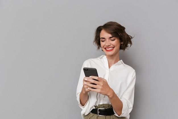灰色の壁に隔離、笑顔と携帯電話を保持している白人女性