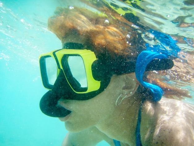 Кавказская женщина с маской и трубкой на пляже под водой