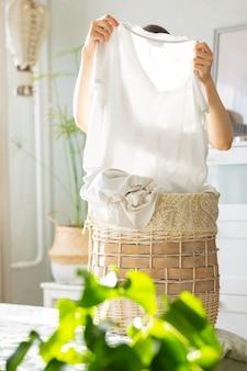 Кавказская женщина сортирует грязную корзину для белья в домашней прачечной