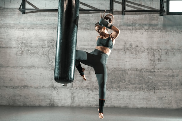 Caucasian woman in sportswear and with boxing gloves kicking bag in the gym. full length.