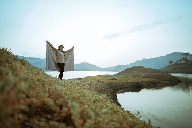 Caucasian woman standing by a lake with blanket