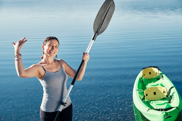 手に櫂を持って緑のカヤックの近くに立って、スポーツの練習に招待された白人女性。