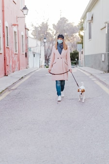 Caucasian woman in the street wearing protective mask and walking with her dog. corona virus concept