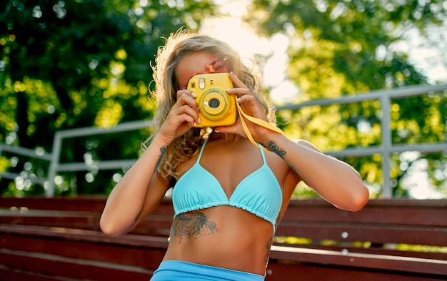 Caucasian woman in a swimsuit and roller skates photographing her friend in a skate park.