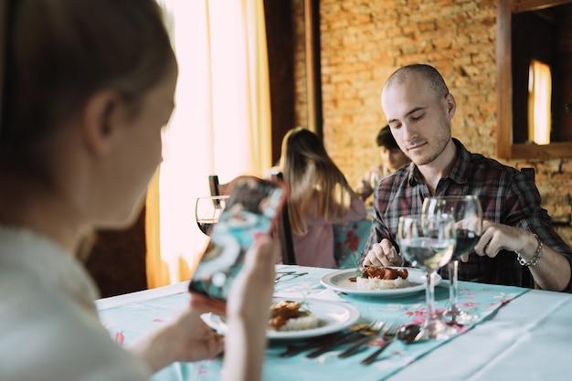 Кавказская женщина фотографирует своего партнера и его еду в ресторане