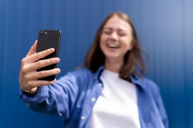 Кавказская женщина делает селфи со своим смартфоном Premium Фотографии