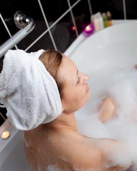 Caucasian woman taking in a bubble bath