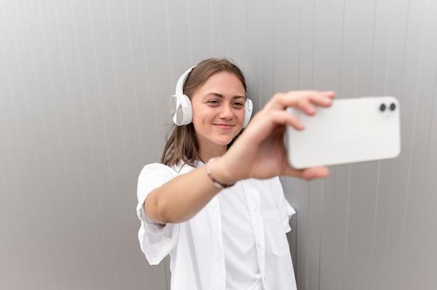 Donna caucasica che si fa un selfie con il suo smartphone