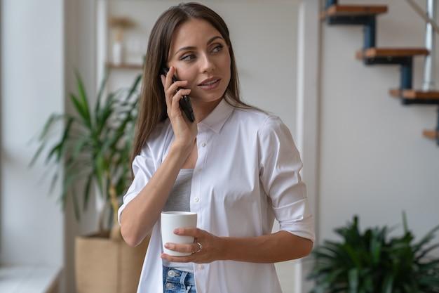 Caucasian woman talking on mobile phone, looking away, holding white mug, drinking coffee or tea