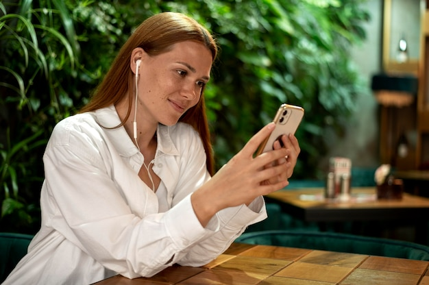 Кавказская женщина пишет кому-то на своем смартфоне