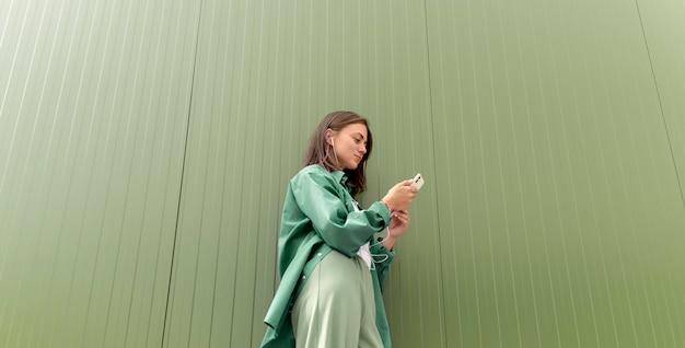 彼女のスマートフォンで誰かにテキストメッセージを送る白人女性