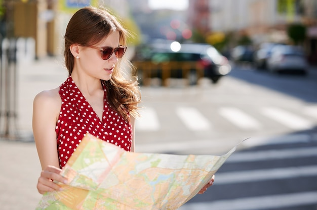 Caucasian woman traveler in sunglasses uses paper map in the summer city outdoors