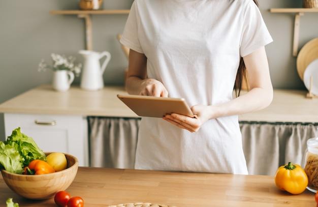白人女性は台所でタブレットコンピューターを使用します