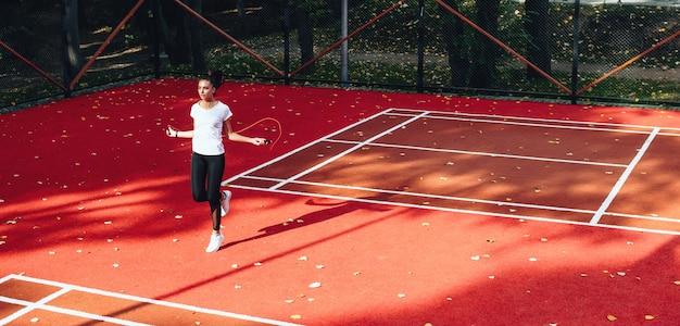 아침 운동을하는 테니스 경기장에서 줄넘기를 사용하는 백인 여자