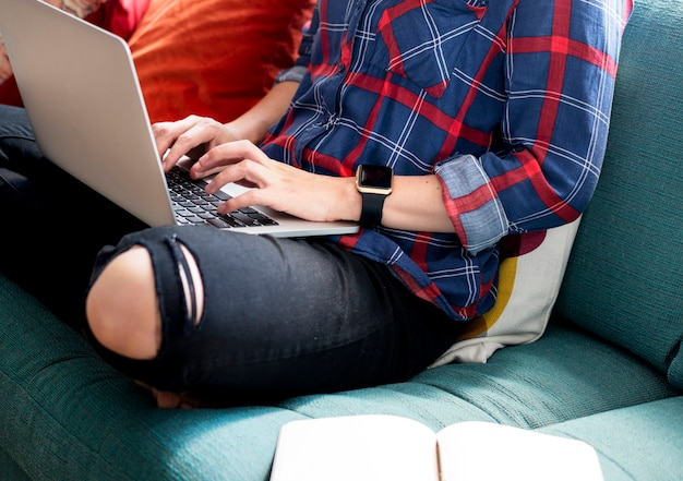 Caucasian woman using a laptop on the couch