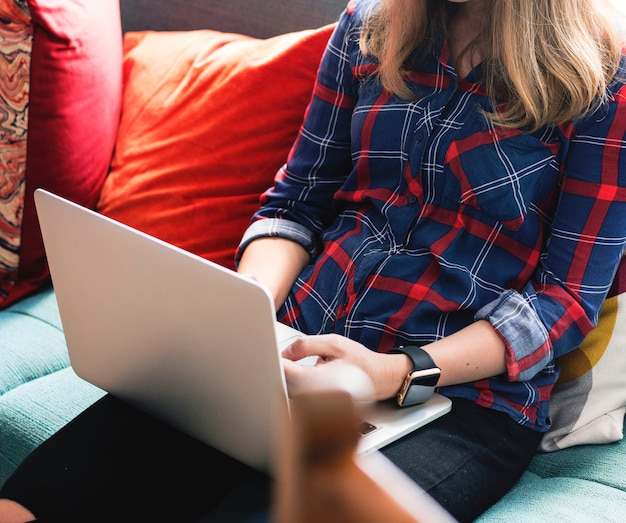 Caucasian woman using laptop on the couch