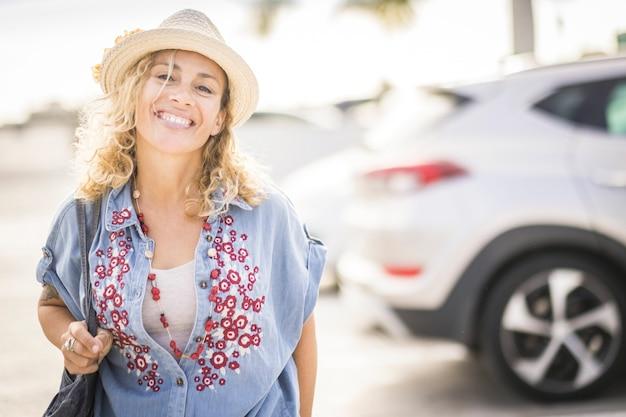 白人女性がバックグラウンドで駐車車をバックに通りを幸せに歩く-人々は都会のアウトドアレジャー活動を楽しむ-スタイリッシュなトレンディな女性の笑顔とライフスタイルを楽しむ