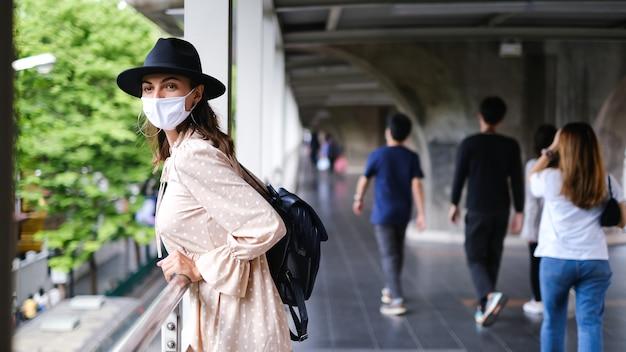 방콕 시내에서 유행병 동안 의료 얼굴 마스크에 지하철 교차점을 걷고 백인 여자.