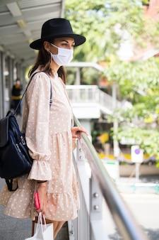 La donna caucasica che cammina sul passaggio della metropolitana in maschera medica mentre la pandemia nella città di bangkok.