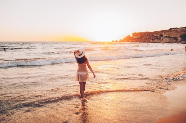 Caucasian woman walks along beautiful seashore