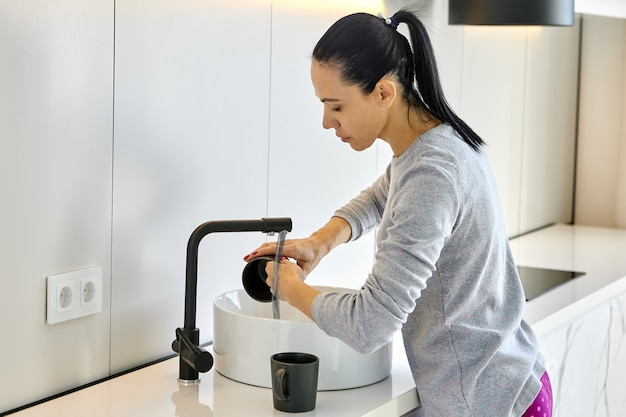 Caucasian woman washes dishes in kitchen sink
