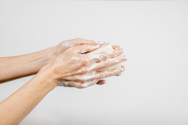 흰 벽에 고립 된 거품 비누로 그녀의 손을 씻는 백인 여자