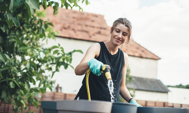Caucasian woman watering some pot after planting flowers while smile in the yard