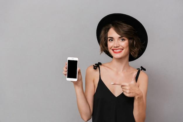 灰色の壁に隔離されたスマートフォンを保持している黒いドレスと帽子を身に着けている白人女性