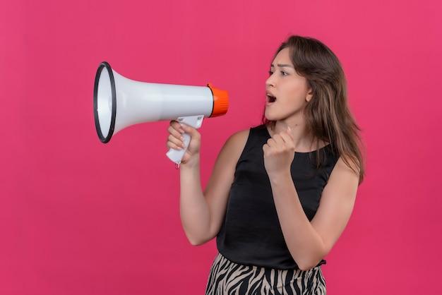黒のアンダーシャツを着ている白人女性はピンクの壁にスピーカーを通して話します
