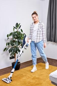 Кавказская женщина в повседневной одежде убирает пол дома в гостиной с помощью современного пылесоса во время пребывания дома, используя свободное время для повседневной уборки дома