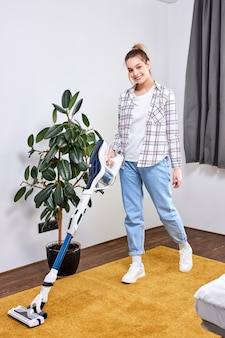 Caucasian woman wearing casual clothes cleaning house floor in living room using modern vacuum cleaner during staying at home using free time about daily housekeeping routine, at home