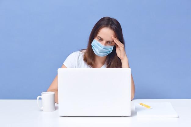 Кавказская женщина носить защитную маску, сидя перед ноутбуком