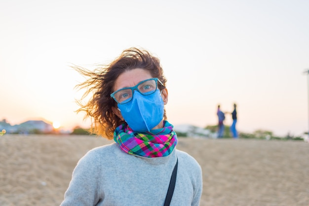 Caucasian woman wearing sanitary mask outdoors in nha trang beach, famous travel detination in vietnam. tourist with medical mask protection against risk of covid-19 virus pandemic