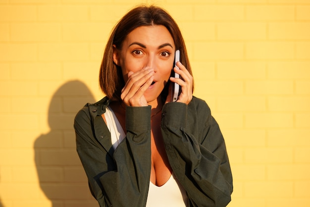 Кавказская женщина в рубашке на закате на желтой кирпичной стене на открытом воздухе позитивные разговоры по мобильному телефону, сплетня, рассказывающая секретный прикрытый рот рукой