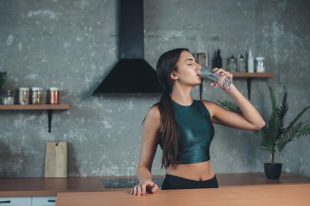 スポーツウェアを身に着けている白人女性は、台所で彼女の体を水和するためにコップ一杯の水を飲んでいます