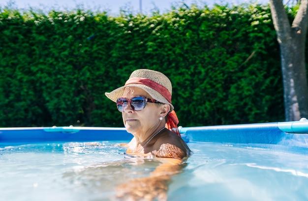 A caucasian woman wearing sunglasses and a hat enjoying her swimming pool at home on a summer day
